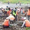 写真: 海岸で懸命に行方不明者の集中捜索をするボランティアら=11日午前11時10分、気仙沼市波路上明戸